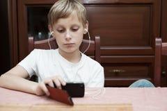 Jongen met hoofdtelefoons die bij de lijst zitten en smartphone onderzoeken stock foto's