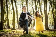 Jongen met kaap en meisje in prinseskleding stock fotografie