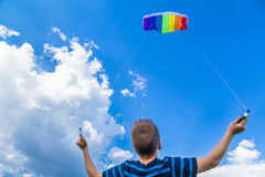 Jongen met kleurrijke vlieger tegen blauwe hemel Royalty-vrije Stock Fotografie