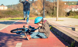 Jongen met knieverwonding na het vallen weg aan fiets Stock Foto