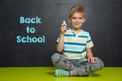 Jongen met krijt en schoolraad met tekst TERUG NAAR SCHOOL Stock Afbeeldingen