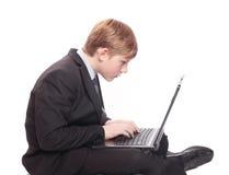 Jongen met laptop die op wit wordt geïsoleerdc Royalty-vrije Stock Foto's