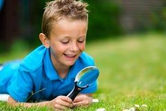 Jongen met meer magnifier Stock Foto