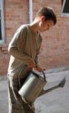 Jongen met metaal water geven-pot tegen brickwall Stock Foto's