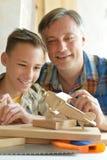 Jongen met model van schip en handsaw stock foto