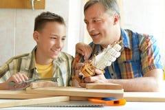 Jongen met model van schip en handsaw stock afbeeldingen