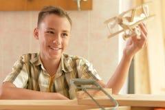 Jongen met model van vliegtuig en handsaw royalty-vrije stock foto's