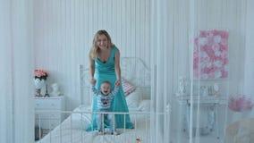 Jongen met moeder die op bed springen stock video
