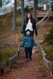 Jongen met moeder op een gang in een pijnboombos stock foto's