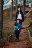 Jongen met moeder op een gang in een pijnboombos royalty-vrije stock fotografie