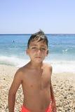 Jongen met mooie groene ogen op het strand stock foto