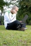 Jongen met notitieboekje en celtelefoon in park Royalty-vrije Stock Fotografie