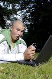 Jongen met notitieboekje en celtelefoon in park stock afbeeldingen
