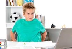 Jongen met oefenboek en PC op tesk Royalty-vrije Stock Foto