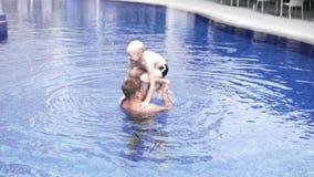 Jongen met papa buiten het spelen in de pool stock footage