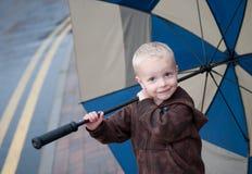 Jongen met paraplu in regen Stock Foto's