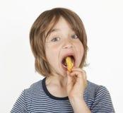 Jongen met pindatikken in de mond Stock Afbeelding