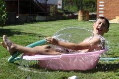 Jongen met plonswater in hete de zomerdag Stock Foto's