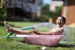 Jongen met plonswater in hete de zomerdag Stock Foto