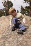 Jongen met rots in schoen Stock Foto