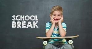 Jongen met skateboard en schoolraad met de ONDERBREKING van de tekstschool Stock Afbeeldingen