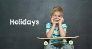 Jongen met skateboard en schoolraad met tekstvakantie Stock Fotografie