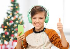 Jongen met smartphone en hoofdtelefoons bij Kerstmis stock foto's