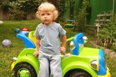 Jongen met stuk speelgoed auto Stock Foto's