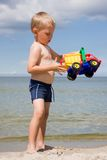 Jongen met stuk speelgoed auto op strand Stock Afbeeldingen