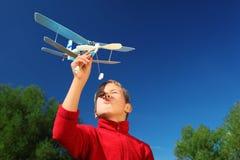 Jongen met stuk speelgoed vliegtuig in handen openlucht Royalty-vrije Stock Foto's