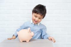 Jongen met varkensspaarvarken kinderjaren, geld, investering en gelukkig mensenconcept stock foto