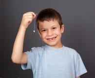 Jongen met verloren tand op draad Royalty-vrije Stock Afbeeldingen