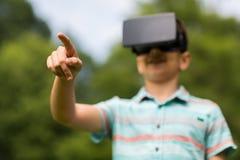 Jongen met virtuele werkelijkheidshoofdtelefoon in openlucht Stock Foto