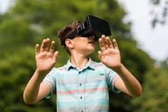 Jongen met virtuele werkelijkheidshoofdtelefoon in openlucht Royalty-vrije Stock Foto