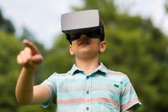 Jongen met virtuele werkelijkheidshoofdtelefoon in openlucht Stock Foto's