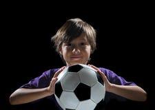Jongen met voetbalbal op donkere achtergrond royalty-vrije stock foto
