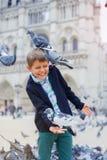 Jongen met vogels dichtbij de kathedraal van Notre Dame de Paris in Parijs, Frankrijk stock fotografie