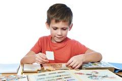 Jongen met zijn geïsoleerde inzameling van oude postzegels Stock Foto