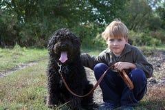 Jongen met zijn hond stock afbeelding