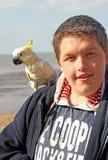 Jongen met zijn huisdierenpapegaai Stock Foto's