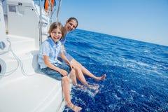 Jongen met zijn zuster aan boord van varend jacht op de zomercruise Royalty-vrije Stock Afbeelding