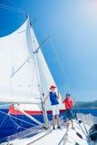 Jongen met zijn zuster aan boord van varend jacht op de zomercruise Royalty-vrije Stock Foto's
