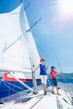 Jongen met zijn zuster aan boord van varend jacht op de zomercruise Reisavontuur, zeilen met kind op familievakantie Royalty-vrije Stock Fotografie