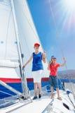 Jongen met zijn zuster aan boord van varend jacht op de zomercruise Reisavontuur, zeilen met kind op familievakantie Royalty-vrije Stock Afbeelding