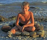 Jongen onder avondgloed op steenachtig strand Royalty-vrije Stock Foto's