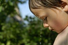Jongen onder een straal van water in de tuin Royalty-vrije Stock Afbeeldingen
