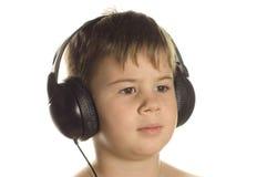Jongen in oortelefoons stock fotografie