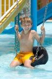 Jongen op bandschommeling in pool Stock Afbeeldingen