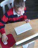 Jongen op computer Stock Foto's