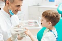 Jongen op cosultation van pediatertandarts die tandkaakmodel gebruiken Royalty-vrije Stock Afbeeldingen